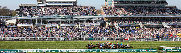 Horse racing finishing post scene with grandstand background